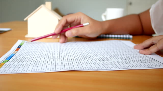 4K-Close-up-shot-hands-of-woman-reading-to-number-in-the-paper-on-table