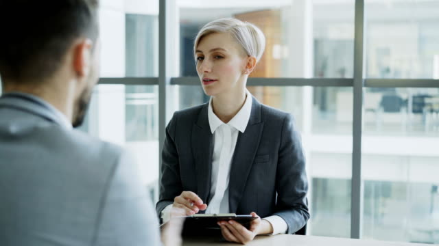 HR-businesswoman-having-job-interview-with-young-man-in-suit-and-watching-his-resume-application-in-modern-office