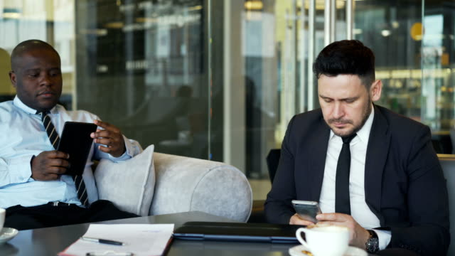 Two-multi-ethnic-businessmen-in-formal-clothes-sitting-and-using-their-smartphone-and-tablet-in-glassy-cafe-during-lunch-time