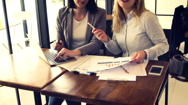 Two-young-beautiful-businesswoman-have-meeting-and-discussing-about-monthly-sale-report-Business-and-finance-concept-