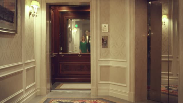 Opening-empty-elevator-in-hallway-luxury-hotel-Woman-entering-in-lift-car