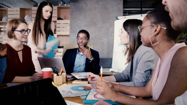 Mixed-race-business-people-meeting-in-office-Secretary-gives-documents-to-boss-he-spreads-them-among-employees-4K