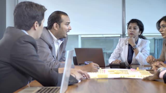 A-motiva-equipo-de-compañeros-de-trabajo-de-oficina-jóvenes-interactuando-en-sala-de-juntas