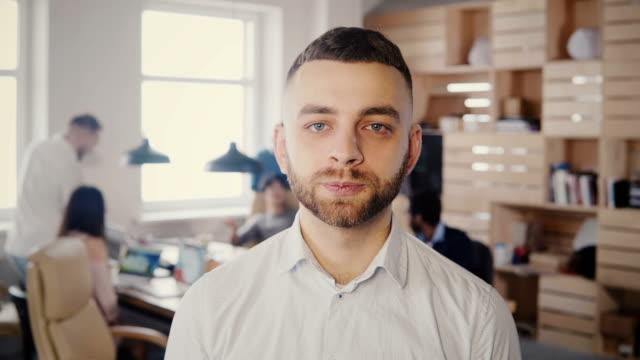 Retrato-de-joven-feliz-empresario-caucásica-posando-en-la-oficina-ocupada-Guapo-macho-trabajador-creativo-mirando-a-cámara-4K