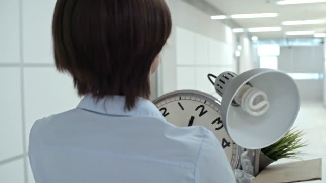 Female-Employee-Carrying-Belongings-in-Office-Hallway