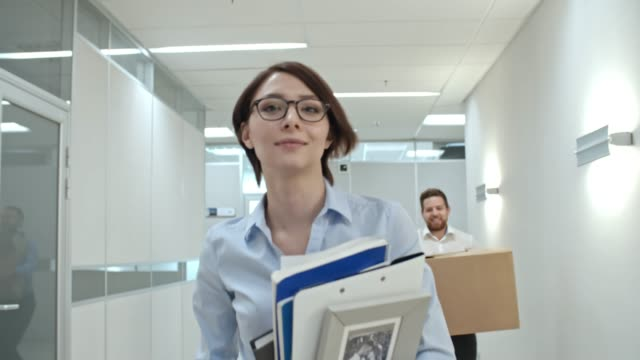 Excited-Colleagues-Running-with-Boxes-in-Office-Hallway
