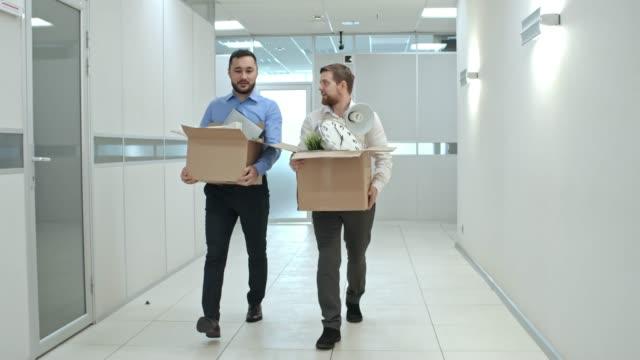 Männer-gehen-mit-hab-und-gut-durch-Büro-Flur