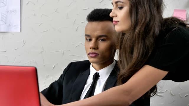Jefe-joven-seduce-a-su-empleado-africana-sexualmente-se-inclina-coquetear-concepto-acoso-50-fps