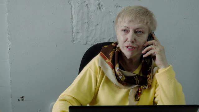 Charla-mujer-jubilada-en-el-teléfono-en-la-oficina