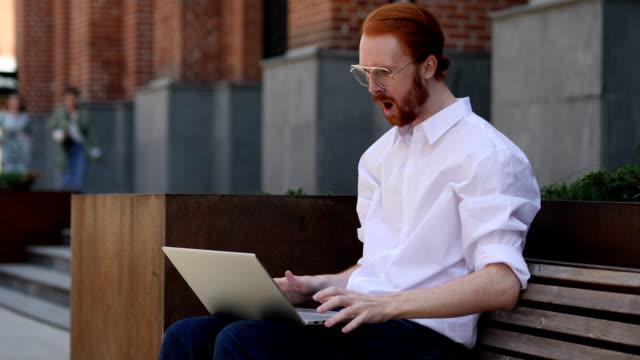 Erstaunt-Fragen-Designer-mittels-Laptop-sitzend-auf-Bank