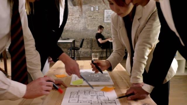 Business-Team-von-gemischter-ethnischer-Herkunft-sind-Holding-Treffen-in-moderne-Bürogebäude-sprechen-und-diskutieren-Projekt