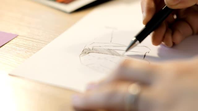 Chica-dibuja-un-lápiz-sobre-el-papel-Diseñador-de-moda-femenina-dibujo-bocetos-Diseñador-de-dibujo-y-pintura-Close-up