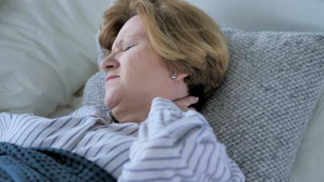 Müde-alte-Senior-mit-Nackenschmerzen-schlafen-im-Bett