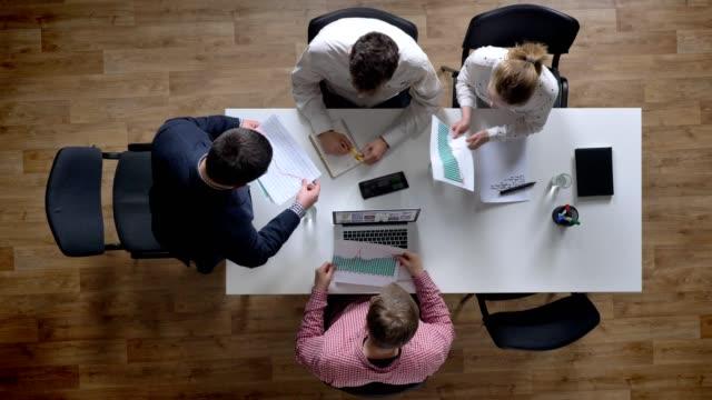 Boss-hereinkommt-und-verleiht-jeder-Topshot-Dokument-Business-team-Holding-Treffen-in-modernen-Büros-Sitzungssaal-overhead