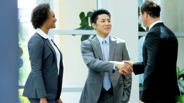 Male-female-multi-ethnic-real-estate-team-handshake