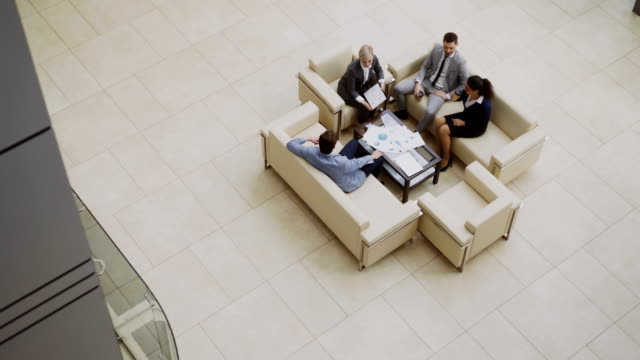 Top-view-of-group-of-business-people-colleagues-discussing-financial-charts-sitting-on-couchs-in-lobby-at-modern-business-center