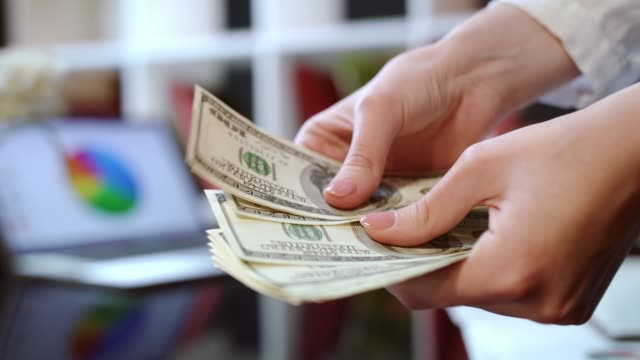 Woman-hands-counting-cash-money-in-office-Business-success-concept