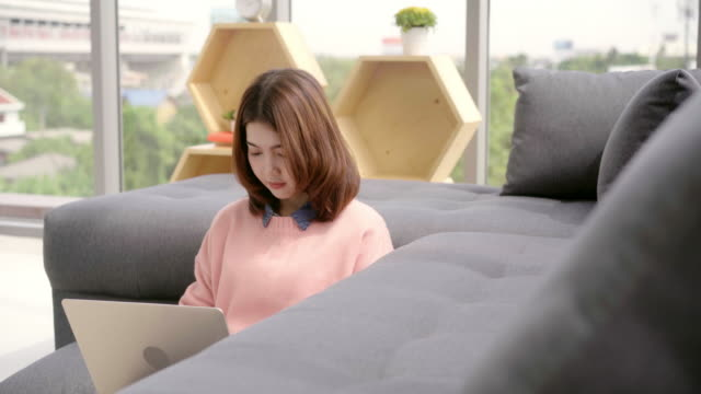 Junge-Asiatin-Forschung-Arbeit-für-ihr-Geschäft-Lächelnde-Frau-sitzend-auf-Sofa-entspannen-beim-Online-shopping-Website-durchsuchen-Glückliches-Mädchen-in-der-Freizeit-zu-Hause-über-das-Internet-Surfen-