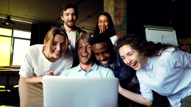Excitada-joven-está-mirando-a-la-pantalla-del-ordenador-portátil-regocijarse-y-expresar-felicidad-sus-colegas-están-felicitándolo-por-éxito-Palmas-de-las-manos-y-tocar-el-hombro-