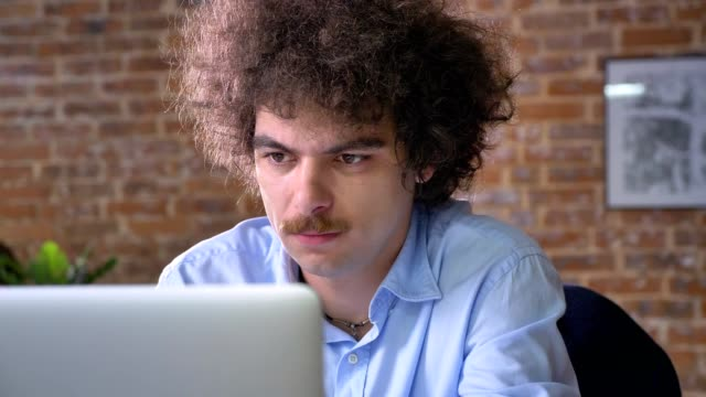Stressed-worker-with-curly-hair-and-mustache-holding-his-head-problems-with-business-modern-office-background