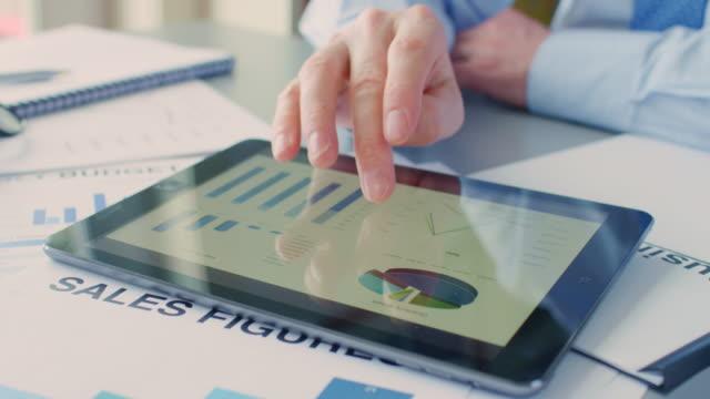 Businessman-Using-Digital-Tablet-Over-Sales-Documents-At-Desk-4K