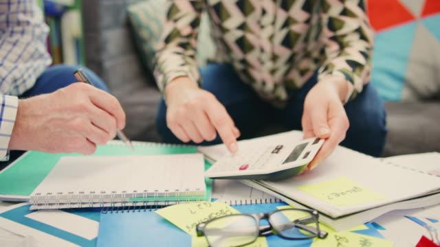 Mujer-mostrando-calculadora-empresario-escribiendo-en-el-Bloc-de-notas-de-4K