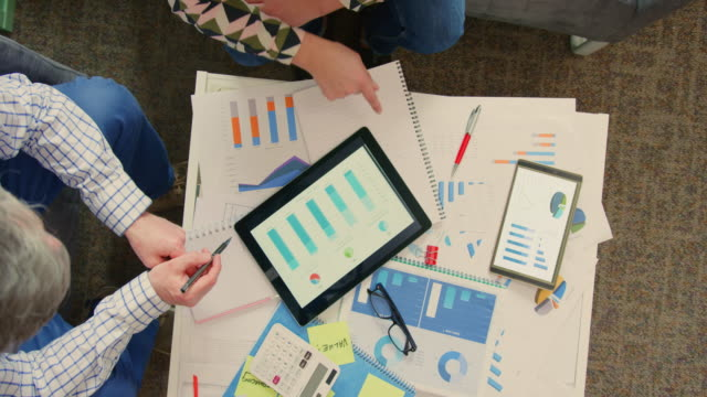 Overhead-View-Of-Coworkers-Analyzing-Financial-Data-On-Digital-Tablet-4K