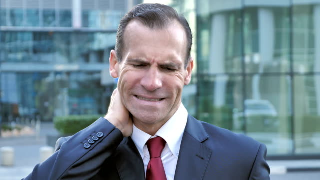 Tired-Middle-Aged-Businessman-with-Neck-Pain