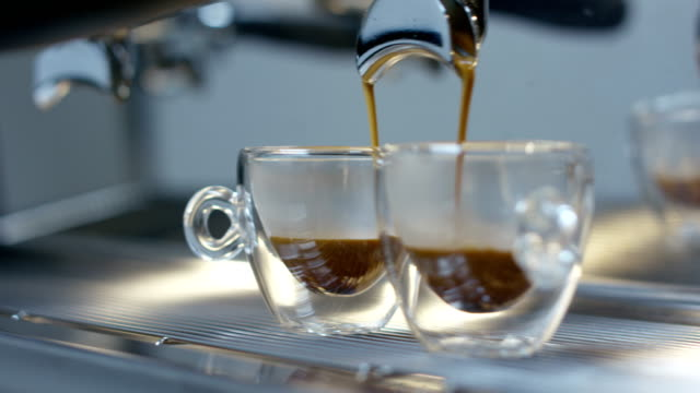 Super-Slow-Motion-von-heißen-Espresso-Kaffee-Gießen-in-ein-zwei-weiße-Porzellantassen-aus-Kaffeemaschine-in-4k-(Draufsicht-Nahaufnahme)