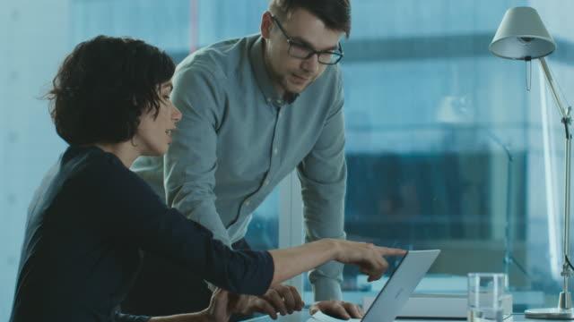 Escucha-Ejecutivo-mujer-hermosa-a-su-jefe-de-proyecto-dando-asesoría-señalando-datos-mostrados-en-un-ordenador-portátil-Empresarios-con-la-discusión-en-la-oficina-