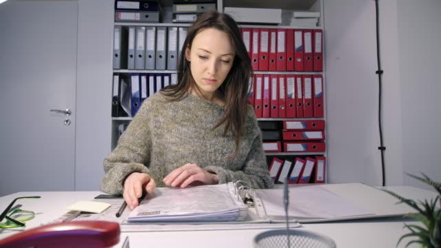Woman-opening-ring-binder