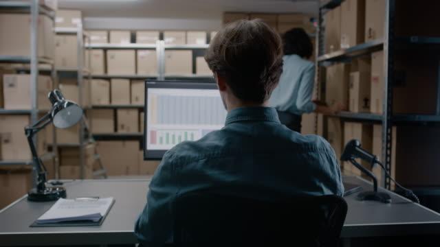 Lager-Inventar-Manager-arbeitet-mit-einer-Tabellenkalkulation-auf-einem-Personal-Computer-sitzend-an-seinem-Schreibtisch-Im-Hintergrund-Regale-voller-Karton-Pakete-für-den-Versand-bereit-