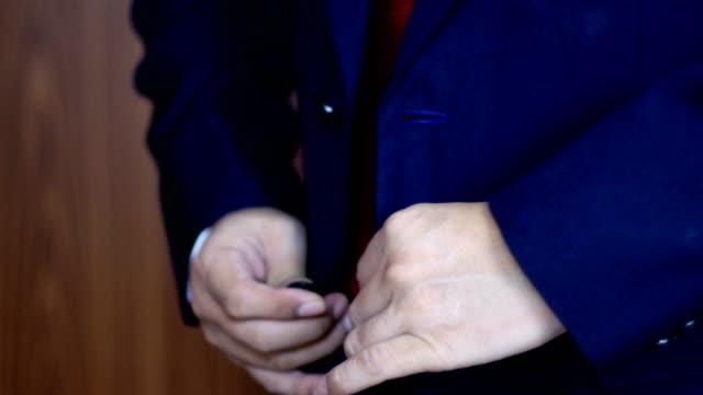 4k-de-cerca-abotonarse-la-chaqueta-hombre-de-negocios-en-un-traje-de-botones-de-fijación-en-su-chaqueta-preparándose-para-salir-