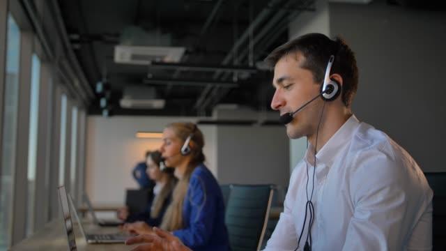 Gut-aussehend-Arbeitskraft-im-Büro-Call-Center-Gespräch-mit-Kunden-und-dann-Lächeln-zu-Kamera
