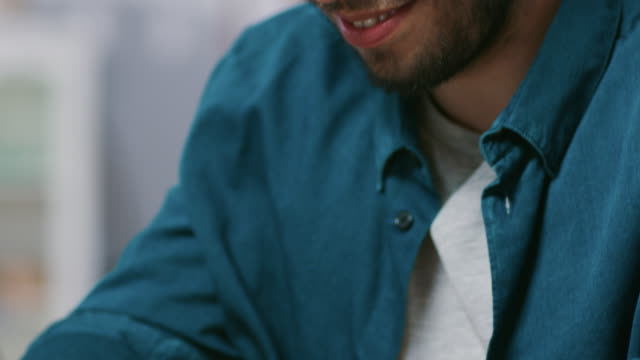 Primer-plano-elevando-la-tiro-de-guapo-escribiendo-en-un-ordenador-portátil-y-sonriendo-