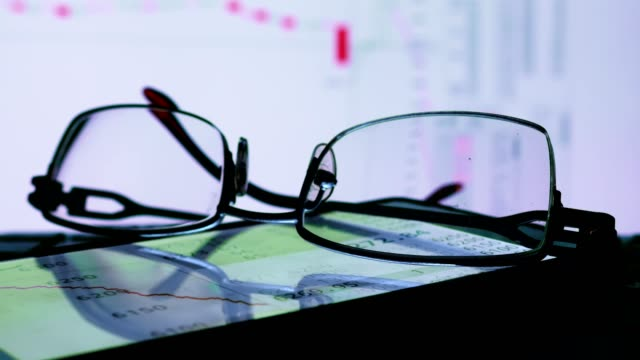 Online-stock-exchange-trade-data-on-a-monitor-and-glasses-
