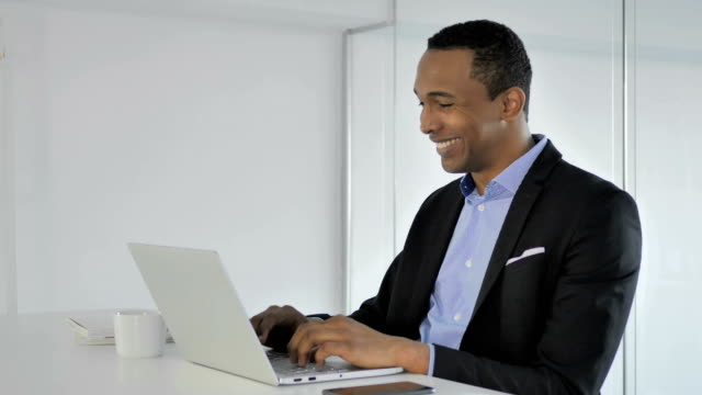 Casual-Afro-American-Businessman-Celebrating-Success-Working-on-Laptop