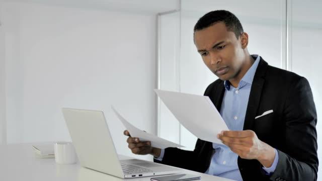 Malestar-ocasional-empresario-afroamericano-reaccionando-no-contrato-informe-lectura