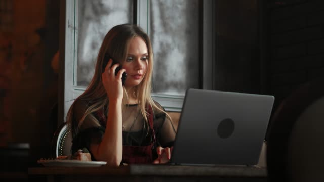 Young-woman-sitting-in-coffee-shop-at-wooden-table-drinking-coffee-and-using-smartphone-On-table-is-laptop-Girl-browsing-internet-chatting-blogging-Female-holding-phone-and-looking-on-his-screen