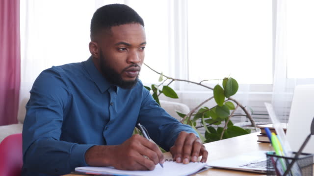 Businessman-using-laptop-and-taking-notes-at-office