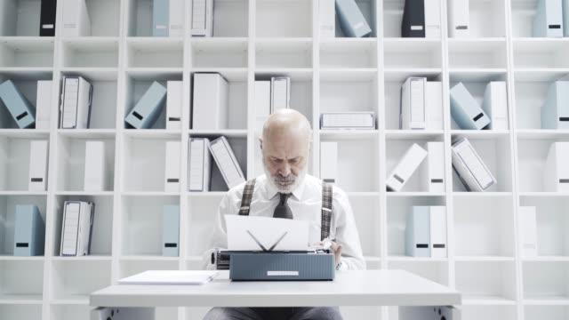 Empresario-Senior-escribiendo-en-una-máquina-de-escribir