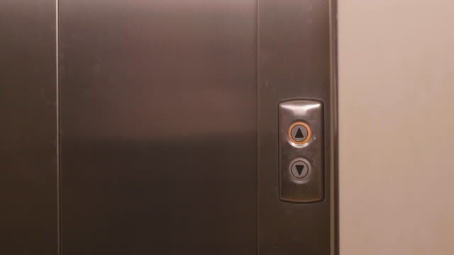 Business-man-pushing-button-for-calling-elevator-and-coming-into-lift