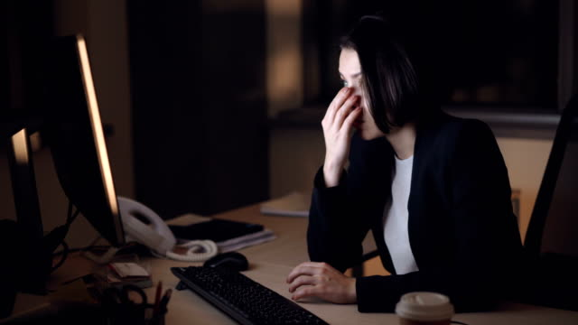 Tired-young-lady-is-working-late-hours-in-office-using-computer-then-rubbing-her-temples-trying-to-reduce-headache-and-fatigue-Technology-and-overwork-concept-
