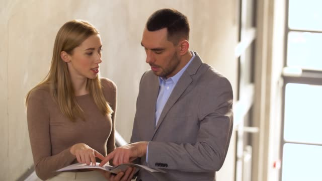 businesswoman-and-businessman-discussing-documents