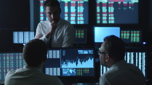 Equipo-de-agentes-de-bolsa-se-están-teniendo-una-conversación-en-una-oficina-oscuro-con-pantallas-