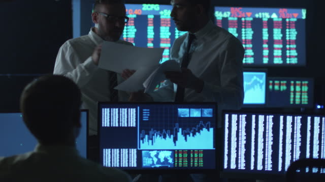 Two-stockbrokers-are-having-an-argument-at-work-in-a-dark-office-with-display-screens-