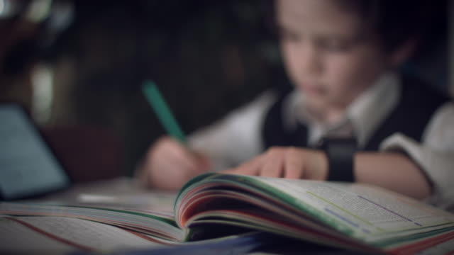 4K-Hi-Tech-Shot-of-a-Child-Doing-Homework-focus-changing-to-book
