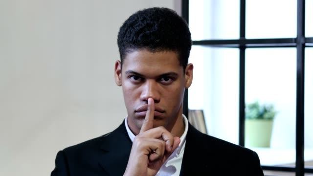 Gesture-of-Silence-by-Black-Businessman-Finger-on-Lips