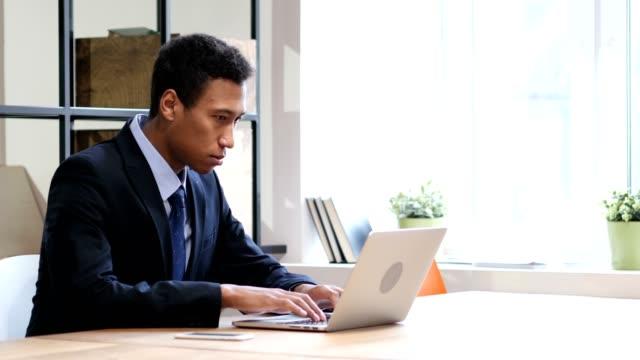 Negro-molesto-empresario-por-pérdida-mientras-trabajaba-en-la-computadora-portátil