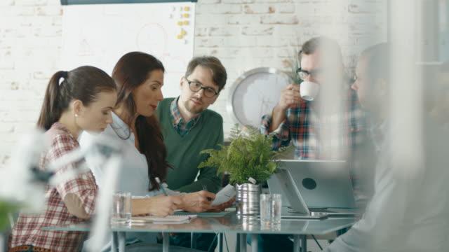 En-Creative-Bureau-sentada-en-el-grupo-de-mesas-de-conferencia-de-seis-compañeros-resuelve-problemas-de-negocios-diarios-